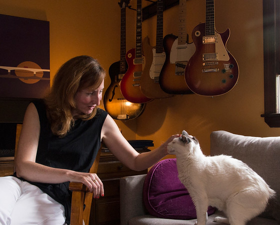 """JIM VAIKNORAS/Staff photo Jen Collins with her cat Lilly in her home office sourounded by her late husband Ted's guitars. Jen has started a foundation """"Tedrock"""" to riase money for music education."""