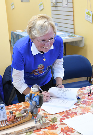 """JIM VAIKNORAS/staff photo Author Donna Seim sign a copy of her book """"Cheeky and Charlemagne"""" at the Joppa Flats Education center."""