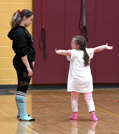 JIM VAIKNORAS/Staff photo Claire Doran shows Maddie Marshall a cheer during a practice at the Nock Middle School in Newburyport.