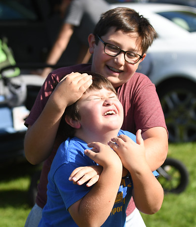 JIM VAIKNORAS/Staff photo Theo Salemi of Newburyport wrestles with his brother Zeph at the American Music and Harvest festival at the Spencer-Peirce-Little Farm in Newbury.