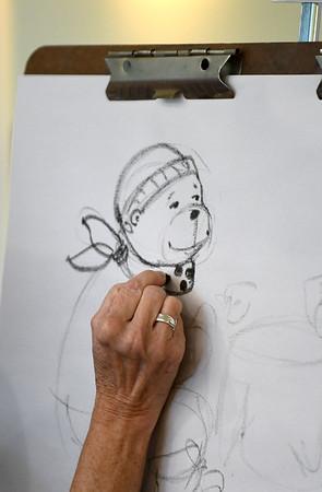 JIM VAIKNORAS/staff photo Illustrator Susan Spellman draws Cheeky and Charlemagne having tea at a reception at the Joppa Flats Education Center.