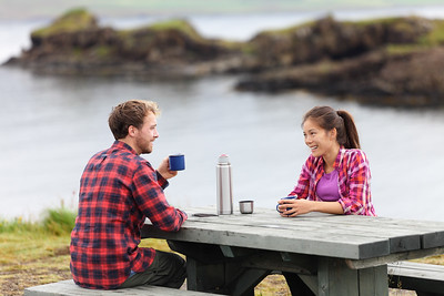 Camping couple sitting at table drinking coffee