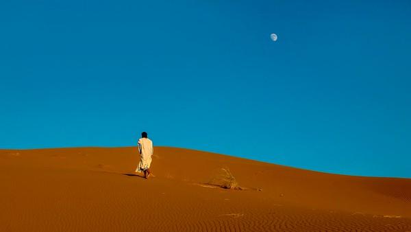 A Moroccan man walks uphill toward the ridge of a sand dune.