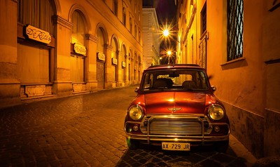 A red Mini parked on a cobblestone street in Rome.