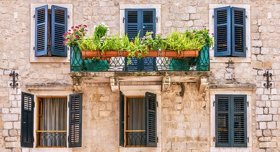 Pretty house facade with shuttered windows and potted plants.