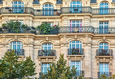 An old, elegant residential building facade in Paris, with ornate details in the stone walls, french doors and wrought iron railings on the balconies.