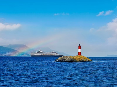 View of the Beagle Channel near Ushuaia, Argentina, where there is a small island with a popular tourist attraction of Les Eclaireurs (the scouts) Lighthouse, with its vibrant red and white bands. A cruise ship and a rainbow are in the background.
