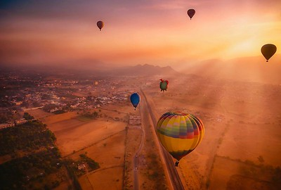 Aerial view of a sunrise scene where sunbeams and hot air balloons carrying tourists fill the colorful sky over Pushkar, Rajasthan.