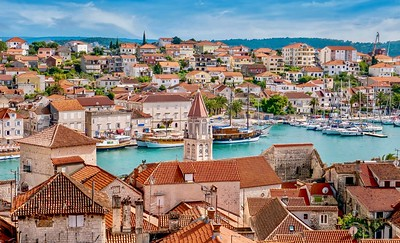 A high angle view of the medieval Old Town of Trogir, Croatia in the foreground, and its newer buildings across the water on the mainland.