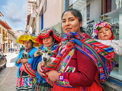 Three Peruvian women dressed in colorful traditional clothing and holding cute lambs and a baby, standing on a sidewalk in Cusco, waiting for tourists to pay for photographing them.