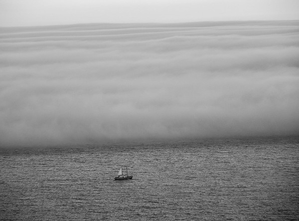 Sailboat racing home against the fog bank