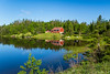 A reflective pond and cottage  in Gros Morne National Park, Newfoundland and Labrador, Canada.