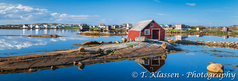 Reflections of fishing stages in the  harbour at the  village of Tilting, Fogo Island, Newfoundland and Labrador, Canada.