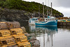 The fishing village harbour with fishing boats, lobster traps and colorful fishing stages at Trout River, Newfoundland and Labrador, Canada.