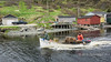 Lobster boat with fish shacks, fishing stages and lobster traps, Trout River, Newfoundland