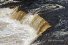 River water coloured by humic acid falls over a ledge in the Humber River, Big Falls, Newfoundland