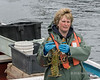 Lobster fisher with her rare green lobster, Trout River, Newfoundland