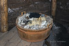 Basket of wools for weaving and knitting sitting in a sod house (Building F), L'anse aux Meadows, Newfoundland