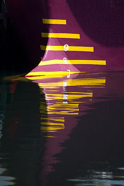 Maroon and Yellow Ship's Bow Reflected in Water