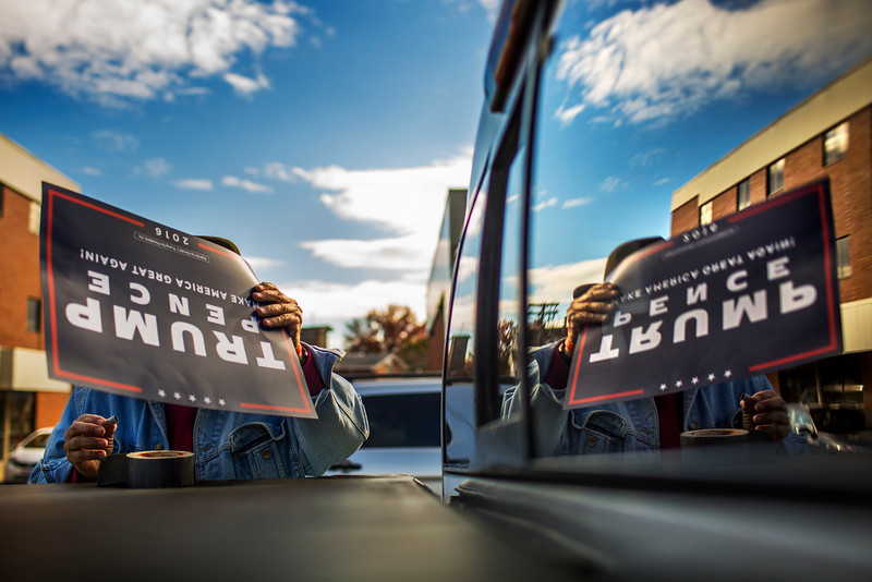 A Donald Trump supporter who chose to remain anonymous duct tapes a Trump Pence 2016 flier to the back of his pickup truck outside of the Trump Headquarters in Manchester, NH on Nov. 5, 2016.
