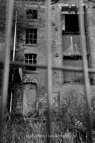 """August 19, 2009<br /> <br /> Abandoned Building<br /> Oldham, UK<br /> <br /> On our way back from Rochdale we came across this abandoned building.  Unfortunately even after 40 or 50 frames this was the best I could come up with.  I would have loved to have got inside but it was fenced up good and I'd had my adventure already a few minutes before I took this shot as I nearly got run over again looking the wrong way while crossing the road.  Several people watched us take photos trying to imagine what could be so interesting about this abandoned building.  The proud locals then announced, """"It was a luxury hotel just last week."""""""