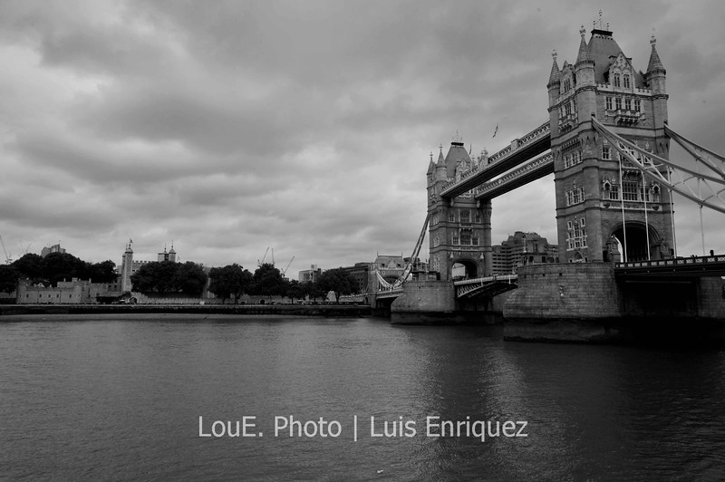 """August 14, 2009<br /> <br /> Tower Bridge<br /> London, UK<br /> <br /> Although my feet were killing me from walking, the excitement and the never ending quest for a great shot led to the Tower Bridge.  There were many Londoners going about their business and seemed quite upset with all of the tourists.  I wondered for a moment if that is how I am in my home town.  Speaking of tourist, don't you just hate it when the family snapper who doesn't know how to use his/her camera is somehow in the middle of your perfect shot?  Then you wait patiently until he/she moves only to have someone else jump in frame.  Don't people know that if one has a BIG professional camera, they should move away and wait until the """"professional"""" has done their shot?  Yeh...I wouldn't move either."""