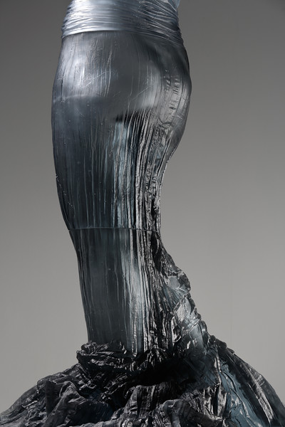 The absent body is visible through the glass dress in this detail of an artwork