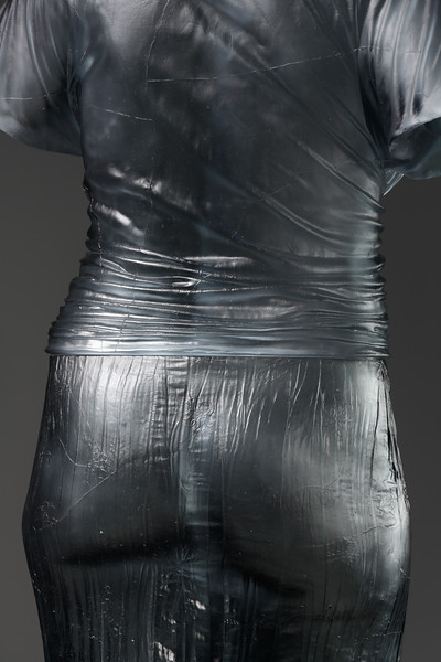 Detail of sculpture showing the impression of an absent body, which can be seen through the carefully rendered fabric in glass