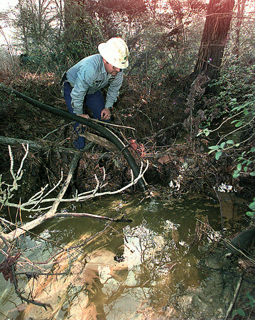 Tom Partain, a vacuum truck operator for Mobley Co. of Kilgore, mans the hose that is being used to remove the petroleum product from the surface of the creek about 20 feet beyond the fence from Longview Refinery on Premier Rd.  Lester Phipps, Jr.