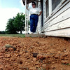 Shirley Bement, daughter of _______________ stands on the back porch of her mother's home where 4 truckloads of dirt was used to fill the abandoned well that took her father's life.   Lester Phipps, Jr.
