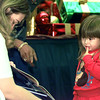 Haley Burleson, 3, hears a story from Crystal Lenore, 16, of Sabine HS during Book Time at Longview Mall Saturday afternoon. The Texas State Teacher's Assn. branch got teachers and some students to read to youngsters at the Food Court. Chris Matula photo.