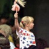 An unidentified girl in the crowd patriotically waves her Barbie doll while watching Clinton speak. Chris Matula photo.