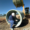 Chris Porter of Porter Services removes bags of concrete from a storm drain pipe Friday morning as he and others prepare to install the drain system for the new Lowes location on North Fourth Street. by darlene