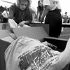 Linda Reaves, left, and Mitzi Hortman sort through AlleyFest t-shirts to be given out to volunteers during the festival-Longview Partnership mixer on the corner of Methvin and Green Streets Tuesday evening. Matula photo.