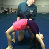 Nikki Bain helps Jessica Harris, 7, with her stretching at Piney Woods Gymnastic Training Center. Matula photo.
