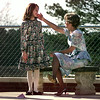 """Elizabeth Wingfield, right, touches her cousin, Megan Knight (9), on the chek as they share a moment alone together during the PT Int.'s """"American Girl"""" tea party Monday afternoon. Matula photo."""