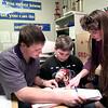 Cory Coleman, left, a tenth grader,  Brandon Orr's , center, a seventh grader, mentor while Jodie Miller tutors children at Ore City Middle School. Kevin green