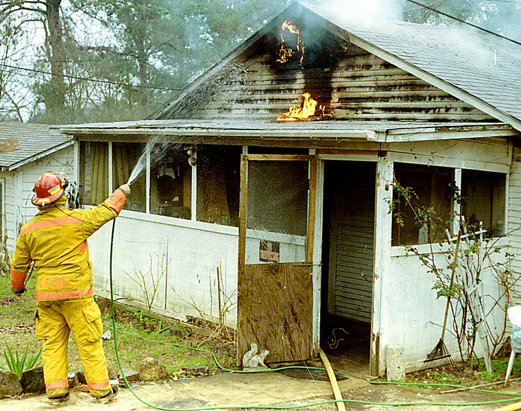 A Longview Firefighter sprays water on the top of a house on fire on 8th St. in Longview Wednesday afternoon, Firefighters were also in the house, as teh fireman outside was commanding the fire and decided to use the owners water hose to spray the outside of the house. Kevin green