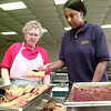 Helen Galley, left, with Marriott Food Service at LeTourneau University, watches as Khalilah Ford, right, a junior at Pine Tree High School restocks the buffet line during her Hospitality Program time at teh University. Kevin green