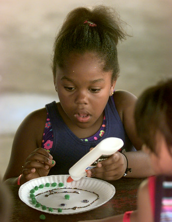 Date:   6/25/98---Arrielle Richardson, the seven year old daughter of Loretta Richardson of Longivew works on a faces during a rec program at Ingram Park Thursday morning in Longview. kevin green