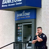 LPD officer Bennie Portwood III stands watch outside the Judson branch of Bank1One after an armed robbery Friday afternoon. Matula photo.