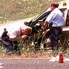 Date:   5/7/98---A Gregg County Deputy unloads a shotgun outside a deputies car Thursday afternoon in the shooting crime scene as another photographs objects on the ground after a bank robber lead police on a 66 mile chase that ended on Texas Highway 31 just south of I-20 in Gregg County. Kevin green