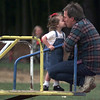 11/09/98---Terry Bailey gives a quick kiss to his step-daughter, Bethany, as they ride the merry-go-round at McWhorter Park Monday. After a weekend of cold and rain, warmer, drier weather brought many people out to play. bahram mark sobhani