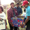 12-17-99---Longview resident Mattie Roseborough, left, smiles as Bethel Baptist Church members Stevie Crain Sr., center, and Derrick Colbert, right, deliver food goods to  her home in hte 1200 blk. of Johns St. Friday afternoon. Bethel will be delivering to 14 families over the next two weeks.Kevin Green