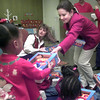12-8-99---Preea Hatten, 3, left, receives a gift from Robin Shaw, right, as Martin Gas employees delivered presents to the Longview Child Development Center Thursday morning in Longview. Kevin Green
