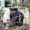 Date:   1/7/99---A Marshall Police Officer searches underneath a house on Frank Street Thursday afternoon after bank robbery suspects lead police on a chase that ended in Marshall. Kevin Green