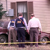 Date:   1/7/99---FBI and Harrison County deputy look inside the suspects car after it crashed in a house on Frank Street in Marshall Thursday afternoon after a police chase and bank robbery in Longview. Kevin green