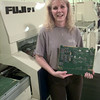 Date:   1/20/99---Alcatel employee Vickie Myers with a computer board that is aassembled by the machine she runs in the background. Kevin green