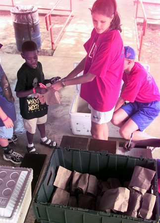 6/15/99---Ryan Terrell,9, left, gets a lunch from staff worker Meredith Walker, right, Tuesday afternoon during the lunch program at Rotary Park in Longview. Kevin green