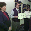 11/3/99---Sam's Club representatives Jimmy Pleasant, center, and Eva Wisdom, left, present a check for $2000 to the Longview Too Ambucs at a meeting Wednesday in Longview. At right is Longview Too Ambucs president Merlyn Homes. bahram mark sobhani